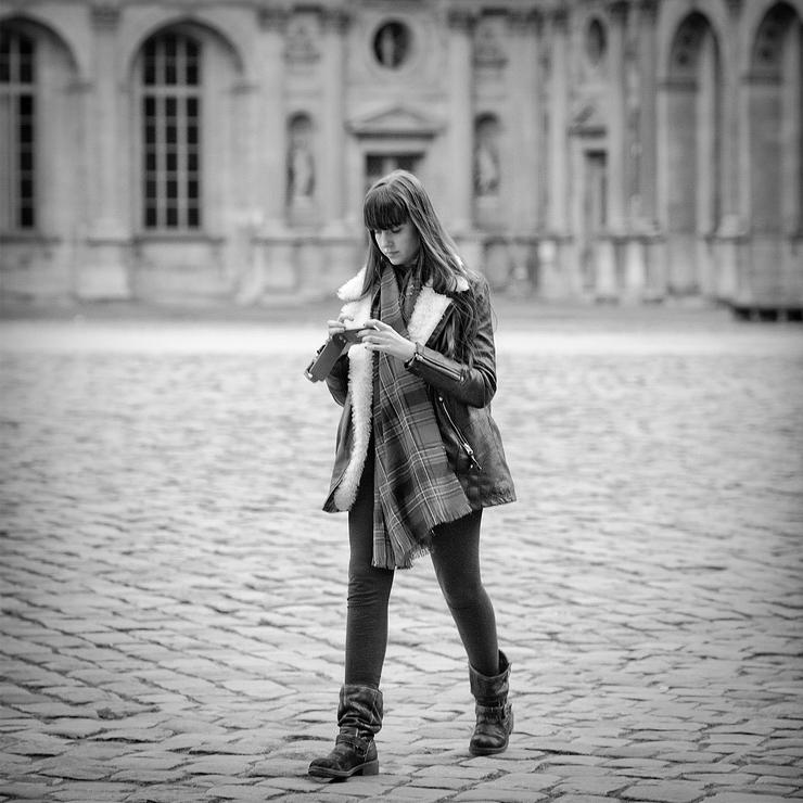 La jeune femme à la longue étole à carreau consultait son smartphone