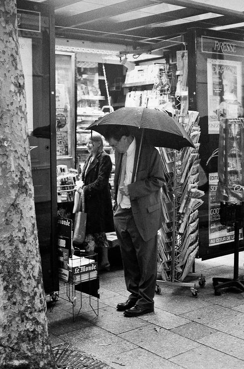 Sous un parapluie à choisir ses journaux
