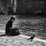 Seule au bord de l'eau à coté de l'oiseau