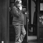 Elle tenait la porte d'un main et fumait une cigarette de l'autre