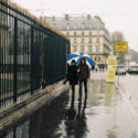 En couple sous un parapluie bleu et blanc